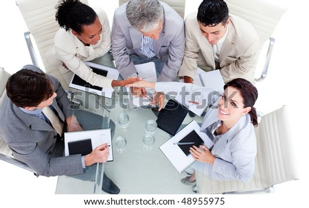 Smiling international business people shaking hands in a meeting - stock photo