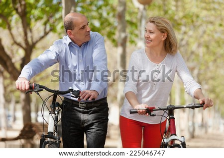 Smiling international couple of active pensioners with bikes  - stock photo