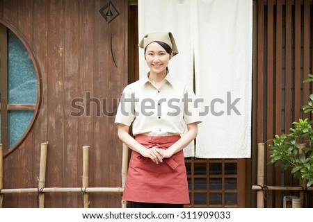 smiling Japanese restaurant clerk outdoor - stock photo