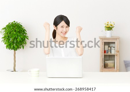 smiling Japanese woman with PC - stock photo