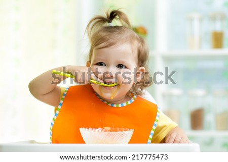 smiling kid eating food on kitchen - stock photo