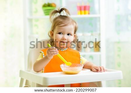 smiling kid eating food on kitchen - stock photo