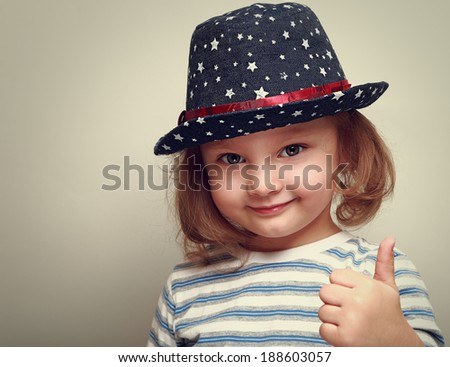 Smiling kid girl in blue hat showing thumb up sign. Closeup - stock photo