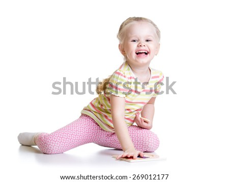 Smiling Kid Girl Solving Puzzle. Isolated on white. - stock photo