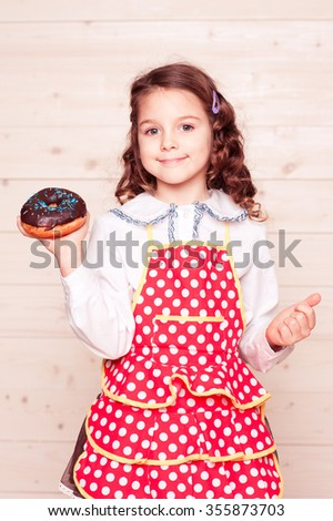 Smiling kid girl 5-6 year old holding chocolate donut in room. Baking. Childhood. Looking at camera. - stock photo