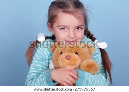 Smiling kid girl 3-4 year old playing with teddy bear over blue. Wearing blue striped hoodie.  - stock photo