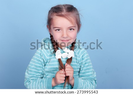 Smiling kid girl 3-4 year old posing over blue. Wearing blue striped hoodie. Holding two braids. Looking at camera.   - stock photo