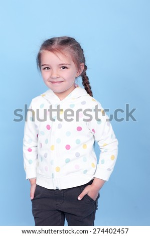Smiling kid girl 3-4 year old with hands in pockets posing over blue. Wearing hoodie and pants. Childhood. Stylish.  - stock photo