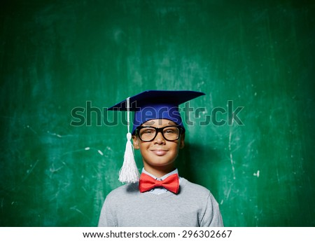Smiling kid in eyeglasses and graduation hat - stock photo