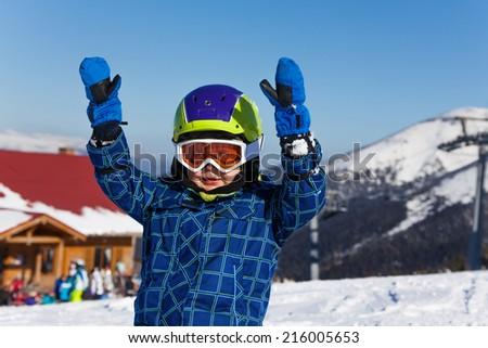 Smiling kid in helmet portrait with hands up on ski resort - stock photo