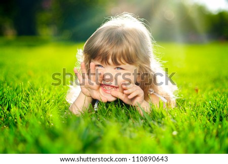 Smiling kid lying on grass - stock photo