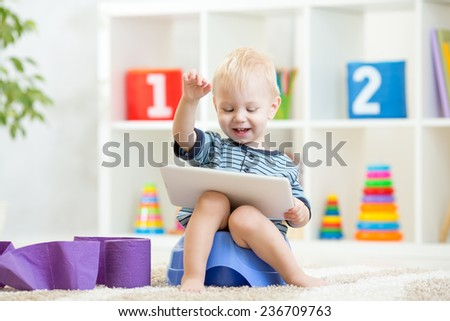 smiling kid sitting on chamber pot with toilet paper rolls - stock photo