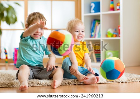 smiling kids boys playing with ball indoors - stock photo