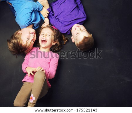 Smiling kids on a blackboard background - stock photo