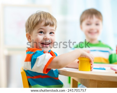 smiling kids painting at home or day care center - stock photo