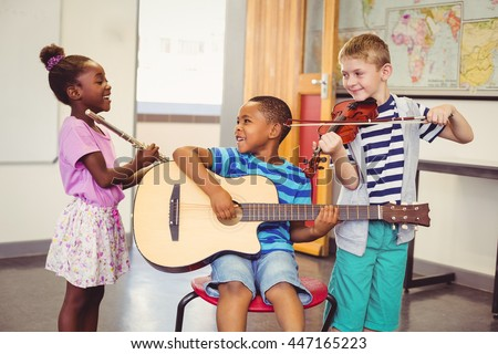 Smiling kids playing guitar, violin, flute in classroom at school - stock photo