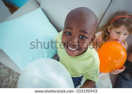 Smiling kids playing with balloons on the couch - stock photo