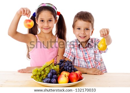 Smiling kids with apple and pear in hands and plate of fruits on the table, isolated on white, isolated on white - stock photo