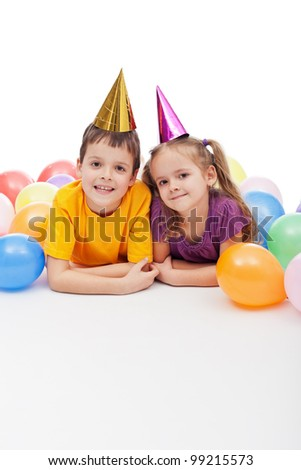 Smiling kids with party hats and balloons laying on the floor - stock photo