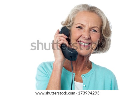 Smiling lady communicating through telephone - stock photo
