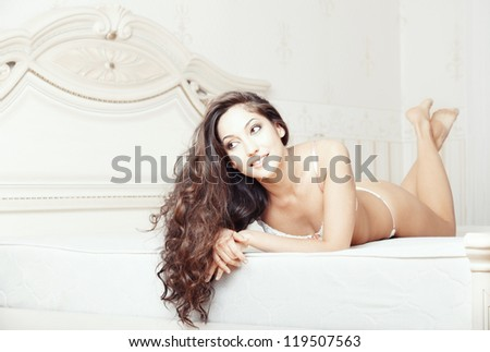 Smiling lady laying and pamepring in bedroom - stock photo