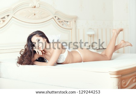 Smiling lady lying and pamepring in bedroom - stock photo
