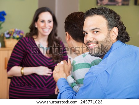 Smiling Latino man with wife and surrogate mother - stock photo