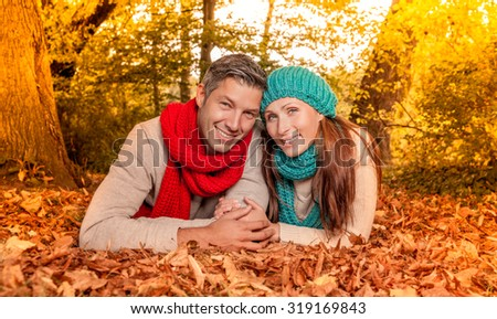 smiling leaves boyfriend with girlfriend on the ground - stock photo