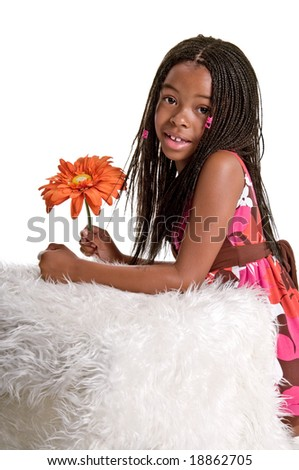 Smiling little African American girl with finger braids with her elbows on the bed holding a large orange flower - stock photo
