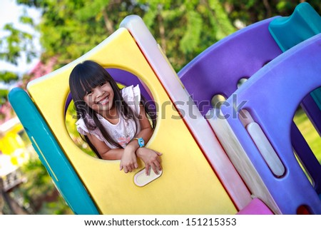 Smiling little asian girl enjoys playing in a children playground - stock photo