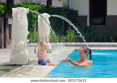 Smiling little baby boy having a fun and laughing with mother playing with splashes in blue pool. Teaching underwater swimming by parents and water amusements during summer family vacation with child - stock photo