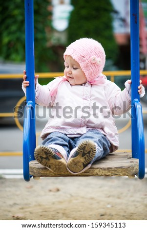 smiling little baby girl in a swing at the park - stock photo