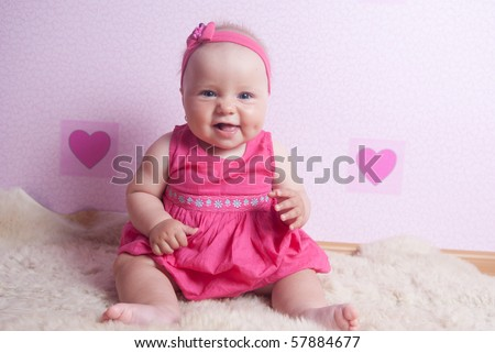 Smiling little baby girl sitting on the carpet at the pink wall with hearts in pink headband and dress - stock photo