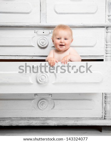 Smiling little baby in a drawer - stock photo