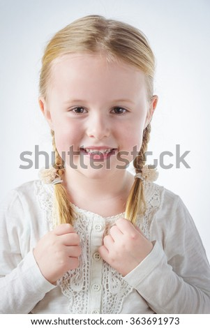 Smiling little blond girl with pigtails - stock photo