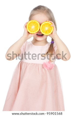 Smiling little blonde girl playing with fresh oranges over white - stock photo