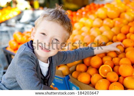 smiling little boy choosing fruits at the market - stock photo