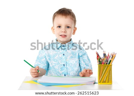 Smiling little boy draws with crayons isolated on white background  - stock photo