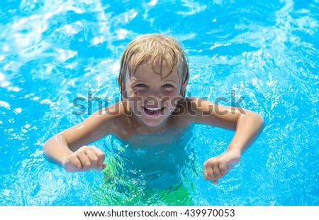 Smiling little boy has fun in swimming pool - stock photo