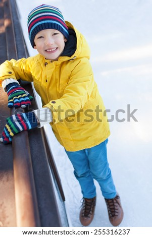 smiling little boy having fun at winter ice skating - stock photo