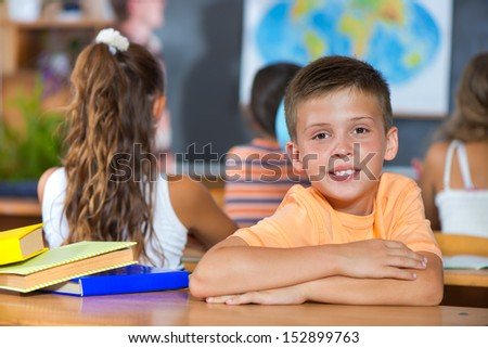 Smiling little boy in classroom at school - stock photo