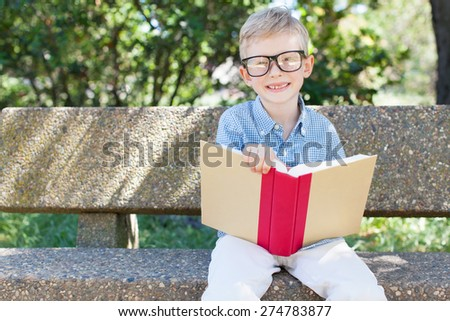 smiling little boy in glasses studying, back to school concept - stock photo