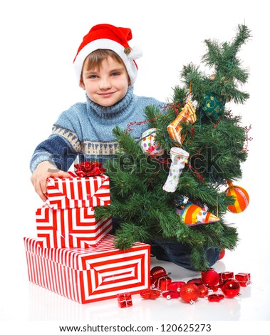 Smiling little boy in Santa's hat with gift box and christmas tree, isolated on white - stock photo