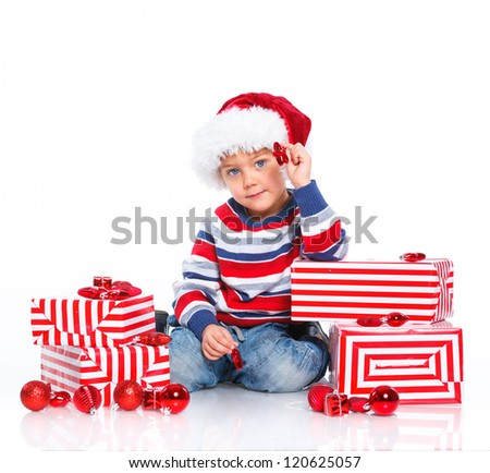 Smiling little boy in Santa's hat with gift box, isolated on white - stock photo