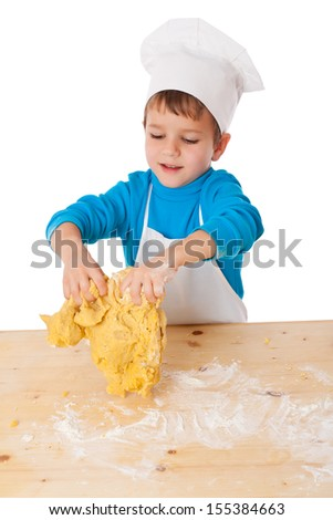 Smiling little boy kneading the dough on the table, isolated on white - stock photo