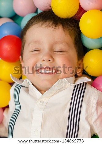 Smiling little boy lying in colorful balls - stock photo