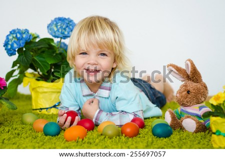 Smiling  little boy lying with Easter eggs  on green carpet - stock photo