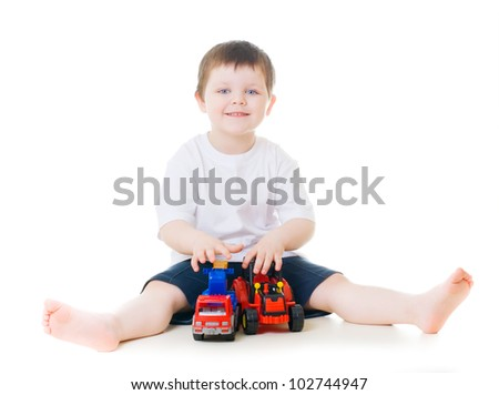 Smiling little boy playing with toy cars - stock photo