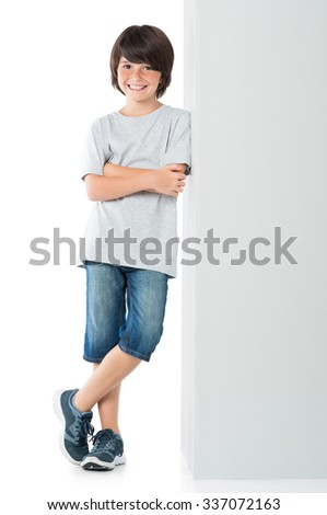 Smiling little boy posing against grey wall isolated on white background. Young boy leaning against a grey sign and looking at camera with arms crossed. - stock photo