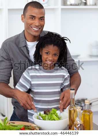Smiling little boy preparing salad with his father in the kitchen - stock photo